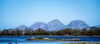 Sheer pink granite mountains overlook the calm, crystal clear water of Oyster Bay | Andrew Wilson