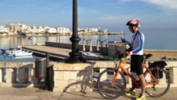 Cyclist on waterfront in Otranto | Kate Baker