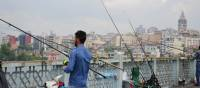 A man fishing from Galata Bridge with the Galata Tower in the background | Erin Williams