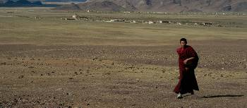 Local Tibetan monk enjoying the open fields and the warm sunlight | Gavin Turner